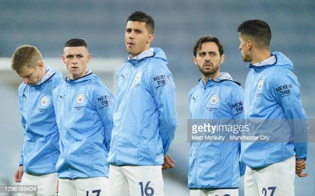 Phil Foden, Rodrigo and Bernando Silva of Manchester City look on as they line up prior to the Premier League match between Manchester City and...