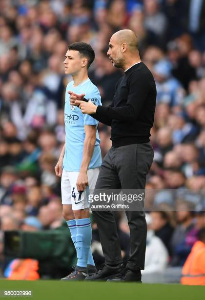 Phil Foden speaks with Josep Guardiola Manager of Manchester City ahead of walking onto pitch during the Premier League match between Manchester City...