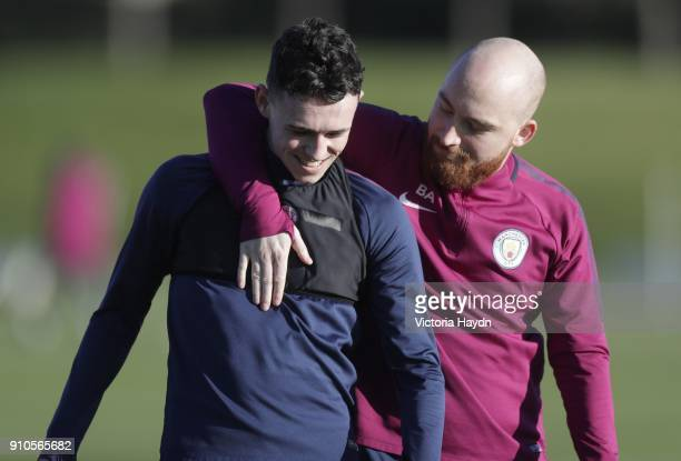 Phil Foden with kitman Brandon Ashton during training at Manchester City Football Academy on January 26 2018 in Manchester England