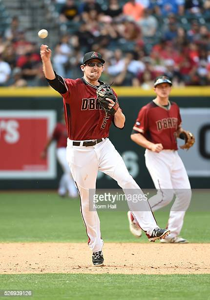 Phil Gosselin of the Arizona Diamondbacks makes a running throw to first base forcing out Nolan Arenado of the Colorado Rockies during the fifth...