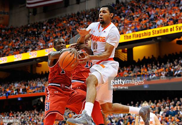 Phil Greene IV of the St John's Red Storm knocks the ball out of the hands of Michael Gbinije of the Syracuse Orange while driving to the basket...