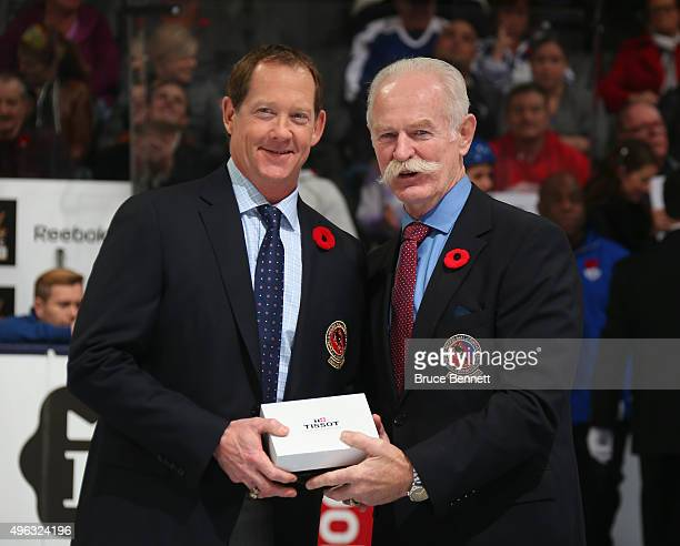 Phil Housley receives his Hockey Hall of Fame blazer from the Chairman of the Hockey Hall of Fame Lanny McDonald prior to the Legends Classic game on...