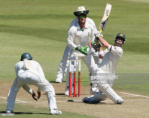 Phil Hughes of Australia hits out with Hashim Amla Mark Boucher and Jacques Kallis of South Africa looking on during day one of the Second Test...