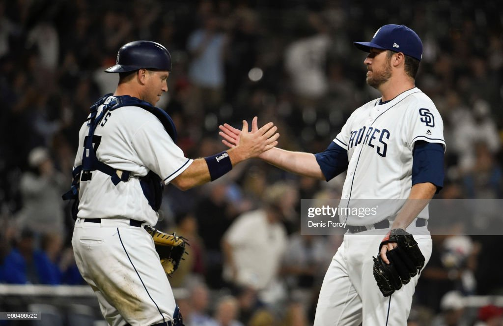 Phil Hughes #59 of the San Diego Padres, (R) is congratulated by A.J. Ellis #17 after getting the final out during the ninth inning of a baseball game against the Cincinnati Reds at PETCO Park on June 2, 2018 in San Diego, California. The Padres won 8-2.