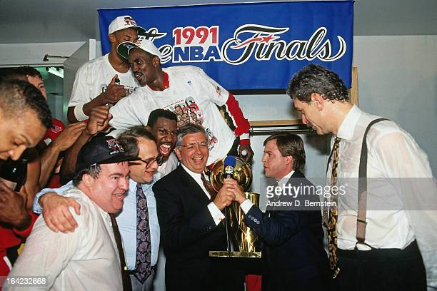 Phil Jackson of the Chicago Bulls is presented the Finals trophy from NBA Commissioner David Stern after winning Game Five of the 1991 NBA Finals on...