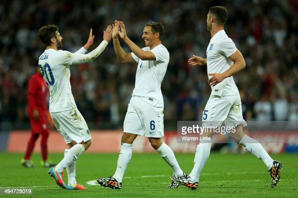 Phil Jagielka of England celebrates scoring the third goal with Adam Lallana and Gary Cahill of England during the international friendly match...