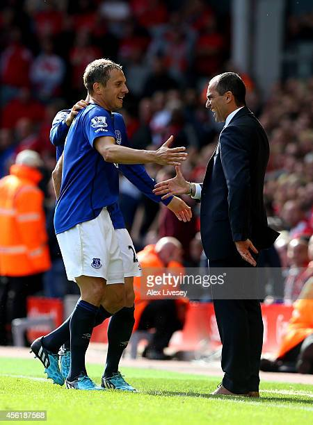 Phil Jagielka of Everton celebrates with Roberto Martinez the manager of Everton after scoring a late goal to level the scores at 11 during the...