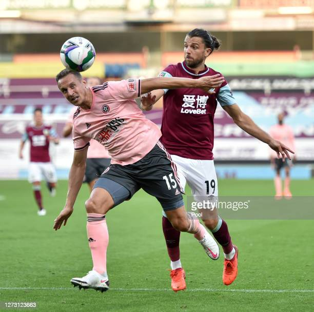 Phil Jagielka of Sheffield United is put under pressure by Jay Rodriguez of Burnley during the Carabao Cup second round match between Burnley and...