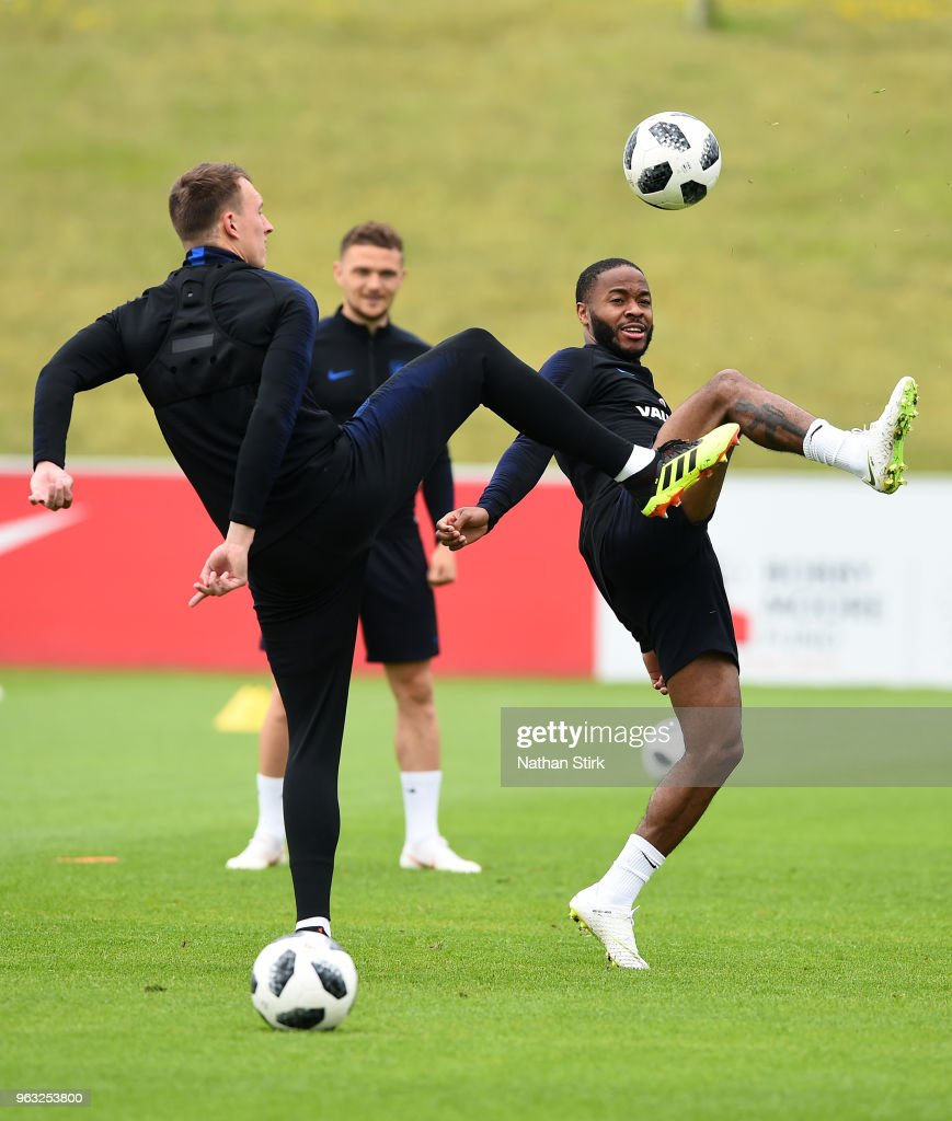 Phil Jones and Raheem Sterling in action during a training session at St Georges Park on May 28, 2018 in Burton-upon-Trent, England.