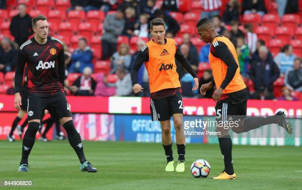 Phil Jones Ander Herrera and Antonio Valencia of Manchester United warm up ahead of the Premier League match between Stoke City and Manchester United...