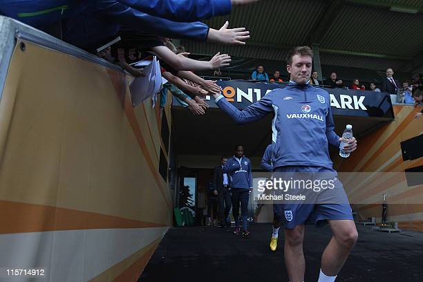 Phil Jones high fives local schoolkids as they walk out from the dressing rooms during the England U21's training session at Montjasa Park Stadium on...