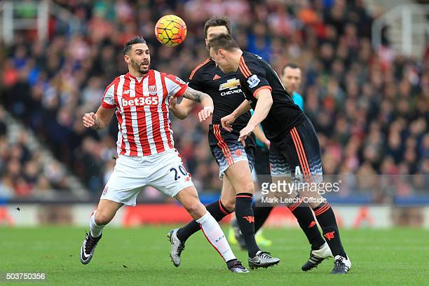 Phil Jones of Man Utd clears with a header from Geoff Cameron of Stoke during the Barclays Premier League match between Stoke City and Manchester...