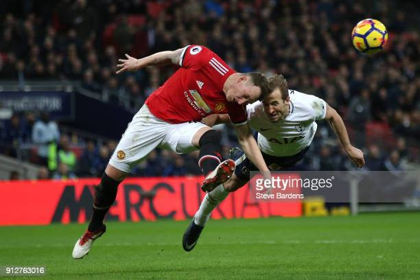 Phil Jones of Manchester United and Harry Kane of Tottenham Hotspur both dive to win a header during the Premier League match between Tottenham...