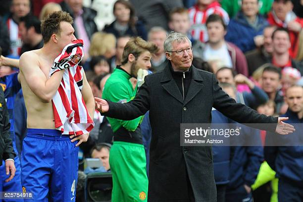 Phil Jones of Manchester United and Sir Alex Ferguson the head coach / manager of Manchester United react after hearing the news that Manchester City...