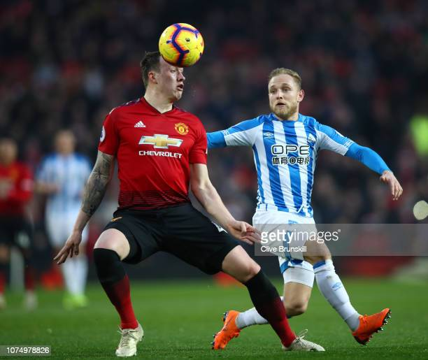 Phil Jones of Manchester United battles for possession with Alex Pritchard of Huddersfield Town during the Premier League match between Manchester...