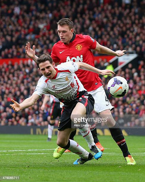 Phil Jones of Manchester United fouls Joe Allen of Liverpool to concede the second penalty kick during the Barclays Premier League match between...