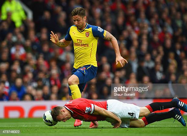 Phil Jones of Manchester United heads the ball clear of Olivier Giroud of Arsenal during the Barclays Premier League match between Manchester United...