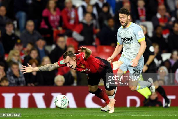 Phil Jones of Manchester United is challenged by David Nugent of Derby County during the Carabao Cup Third Round match between Manchester United and...