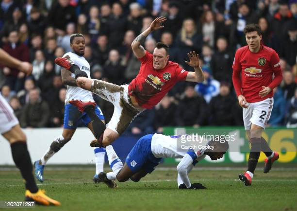 Phil Jones of Manchester United is tackled by Corey Blackett-Taylor of Tranmere Rovers during the FA Cup Fourth Round match between Tranmere Rovers...