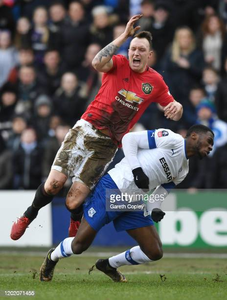 Phil Jones of Manchester United is tackled by Corey BlackettTaylor of Tranmere Rovers during the FA Cup Fourth Round match between Tranmere Rovers...