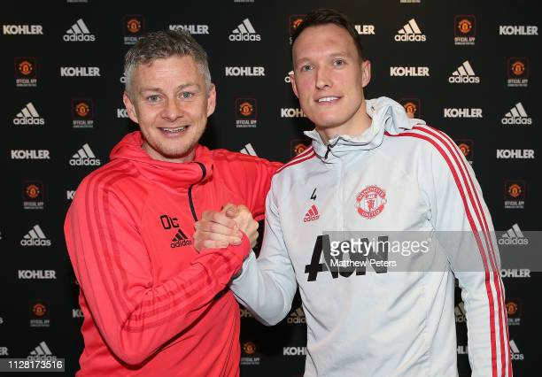 Phil Jones of Manchester United poses with Caretaker Manager Ole Gunnar Solskjaer after signing a contract extension at Aon Training Complex on...