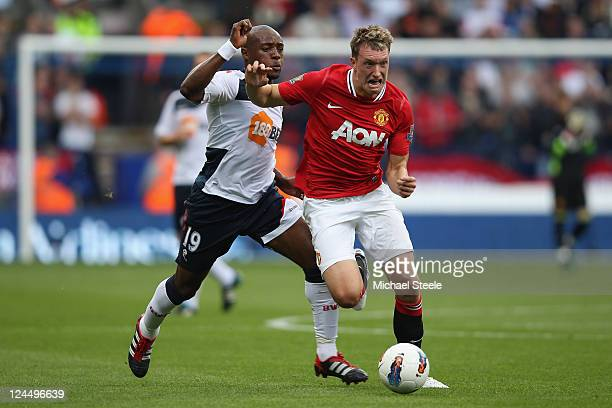 Phil Jones of Manchester United tracked by Nigel Reo-Coker of Bolton Wanderers during the Barclays Premier League at the Reebok Stadium on September...
