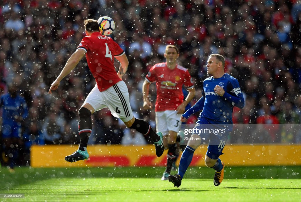 Phil Jones of Manchester United wins a header while under pressure from Wayne Rooney of Everton during the Premier League match between Manchester United and Everton at Old Trafford on September 17, 2017 in Manchester, England.