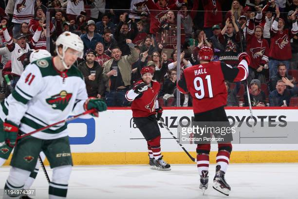 Phil Kessel of the Arizona Coyotes celebrates with Taylor Hall after scoring against the Minnesota Wild during the first period of the NHL game at...