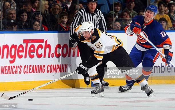 Phil Kessel of the Boston Bruins skates past Josh Bailey of the New York Islanders on April 12 2009 at Nassau Coliseum in Uniondale New York