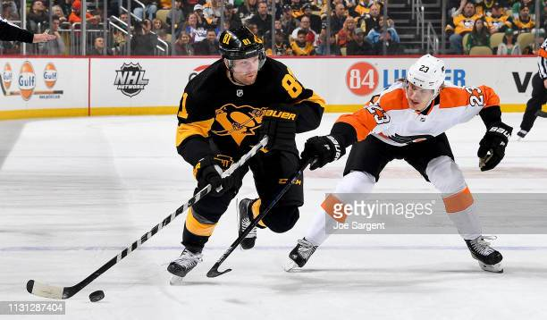 Phil Kessel of the Pittsburgh Penguins handles the puck against Oskar Lindblom of the Philadelphia Flyers at PPG Paints Arena on March 17 2019 in...