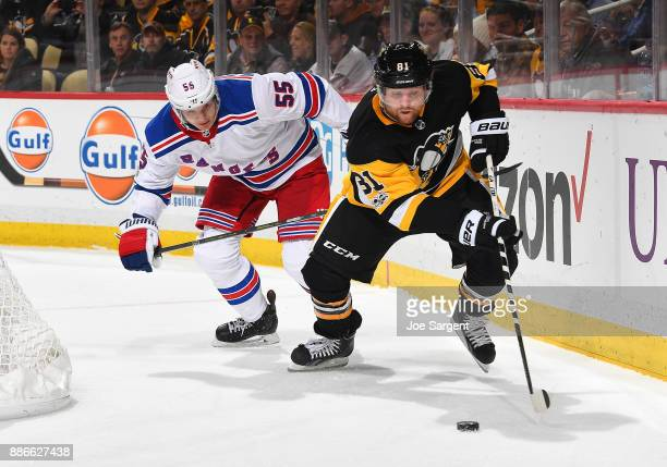 Phil Kessel of the Pittsburgh Penguins moves the puck in front of c of the New York Rangers at PPG Paints Arena on December 5 2017 in Pittsburgh...