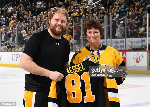 Phil Kessel of the Pittsburgh Penguins poses with a fan during Fan Appreciation night after a 40 win over the Ottawa Senators at PPG Paints Arena on...