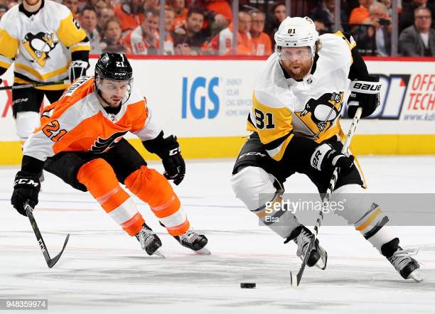 Phil Kessel of the Pittsburgh Penguins takes the puck as Scott Laughton of the Philadelphia Flyers defends in Game Four of the Eastern Conference...