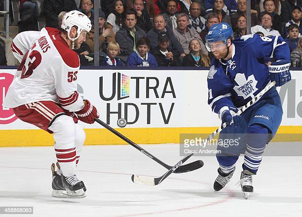 Phil Kessel of the Toronto Maple Leafs tries to get a puck past the defending Derek Morris of the Phoenix Coyotes during an NHL game at the Air...