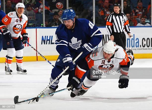 Phil Kessel of the Toronto Maple Leafs tries to get past a diving Nate Thompson of the New York Islanders on December 23, 2009 at Nassau Coliseum in...