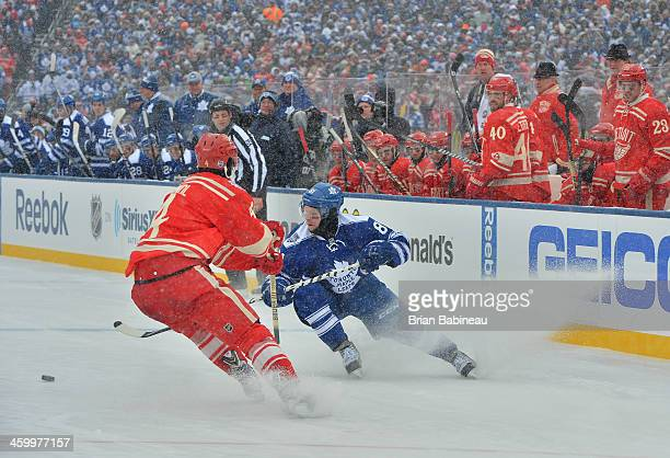 Phil Kessel of the Toronto Maple Leafs turns to play the puck as Jakub Kindl of the Detroit Red Wings looks to defend the play in the first period...