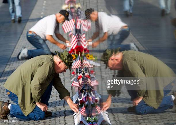 TOPSHOT Phil Layton and Thomas Bogenhagen place cards and flags at the wall of the Vietnam Veterans Memorial in Washington DC on May 28 2017...