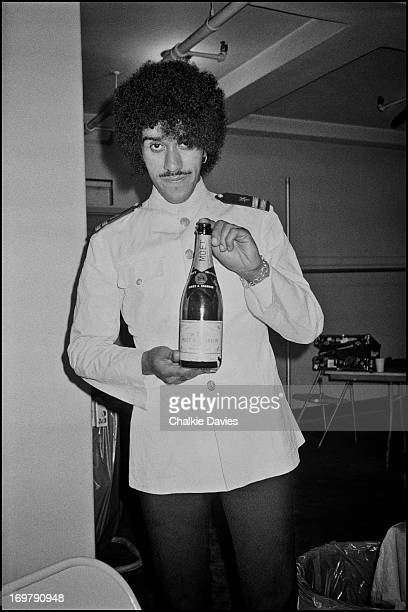 Phil Lynott poses dressed as a waiter holding a bottle of champagne backstage at a Thin Lizzy concert during their 1979 US Tour