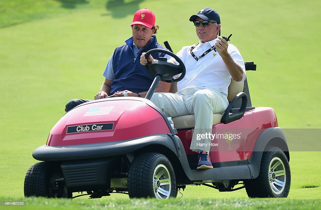 Phil Mickelson and Bill Harmon of the United States team ride a golf cart on the ninth fairway prior to the start of The Presidents Cup at the Jack Nicklaus Golf Club on October 6, 2015 in Incheon City, South Korea.