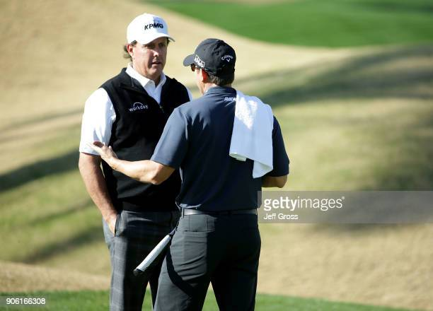 Phil Mickelson and caddie Tim Mickelson talk on the 14th hole during practice for the CareerBuilder Challenge at the Jack Nicklaus Tournament Course...