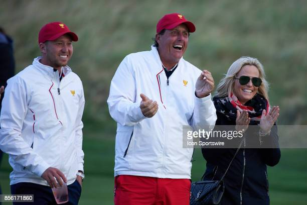 Phil Mickelson and Daniel Berger of the American Team along with Amy Mickelson react to Charley Hoffman's chipin birdie at the 17th hole during the...