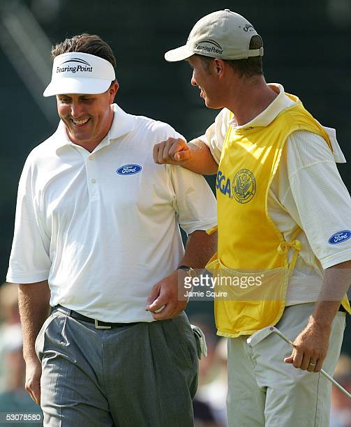 Phil Mickelson and his caddie Jim 'Bones' MacKay celebrate his birdie on the 18th green during round one of the US Open June 16 2005 at Pinehurst...