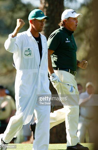 Phil Mickelson and his caddie, Jim Mackay, react to Mickelson's eagle from the 14th fairway during the third round of the the Masters at Augusta...