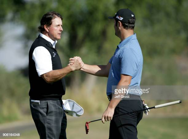 Phil Mickelson and John Rahm of Spain shake hands on the 18th green during practice for the CareerBuilder Challenge at the Jack Nicklaus Tournament...