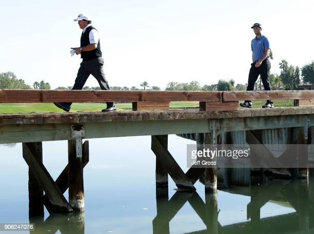 Phil Mickelson and John Rahm of Spain walk across a bridge on the 15th hole during practice for the CareerBuilder Challenge at the Jack Nicklaus...