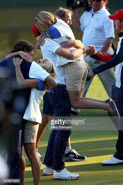 Phil Mickelson and Keegan Bradley of the USA celebrate on the 17th green with Amy Mickelson and Jillian Stacey after defeating the McIlroy/McDowell...