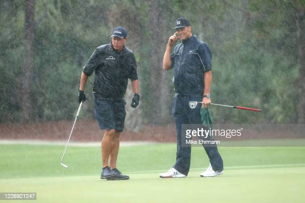 Phil Mickelson and NFL player Tom Brady of the Tampa Bay Buccaneers stand in the rain on the 13th green during The Match Champions For Charity at...