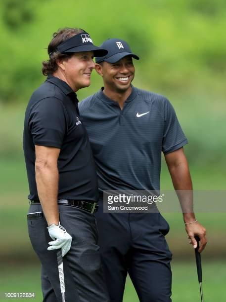 Phil Mickelson and Tiger Woods pose for a picture during a preview day of the World Golf Championships - Bridgestone Invitational at Firestone...