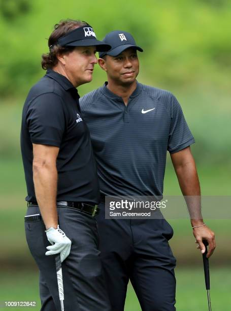 Phil Mickelson and Tiger Woods pose for a picture during a preview day of the World Golf Championships Bridgestone Invitational at Firestone Country...