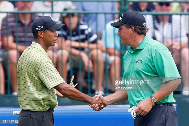 Phil Mickelson and Tiger Woods shake hands before the beginning of the first round of Deutsche Bank Championship, the second event of the new PGA...